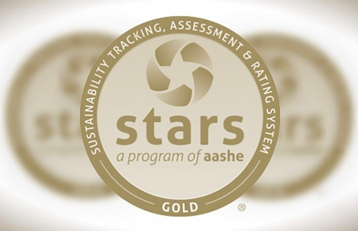 Gold, round symbol with text around perimeter saying Sustainability Tracking, Assessment & Rating System Gold, and STARS a program of AASHE across the center.