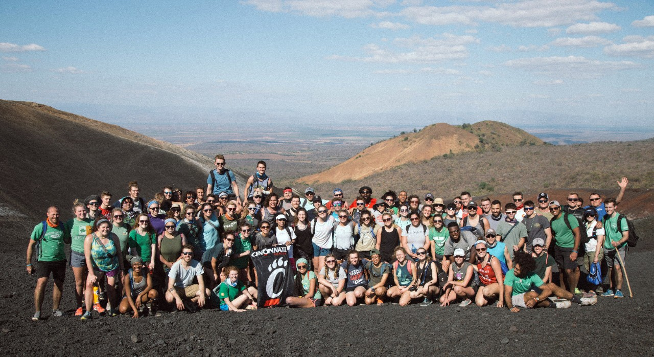 A large group of people pose for a picture in front of mountains