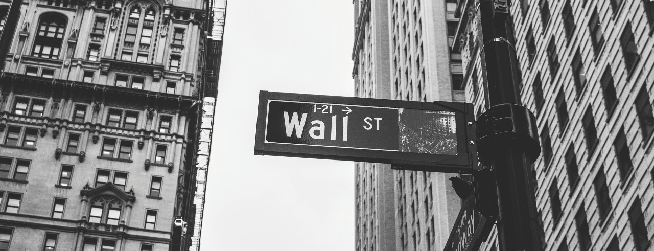 Wall Street sign in New York City with buildings in background.