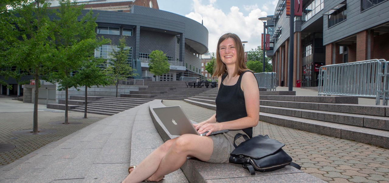 Recent UC grad Ravenna Rutledge sits with laptop along UC's MainStreet.