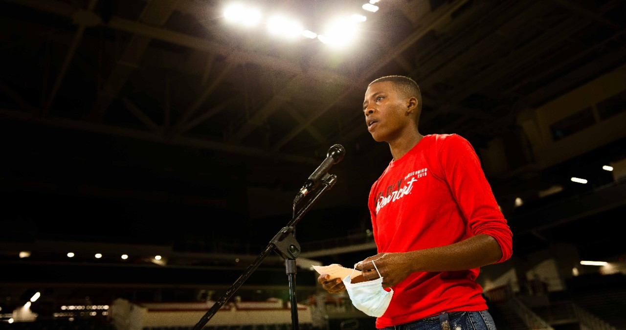 UC graduate Azaria Pittman-Carter stands on stage at an empty Fifth Third Arena reciting a poem she wrote for a taped segment to air during commencement.