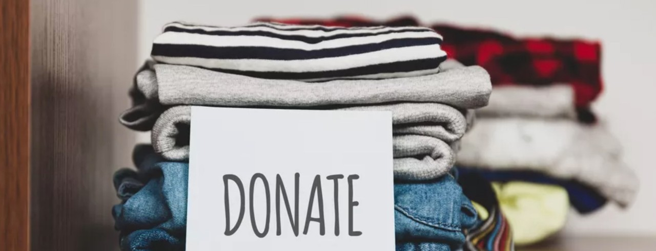 stack of folded clothing with a donation sign