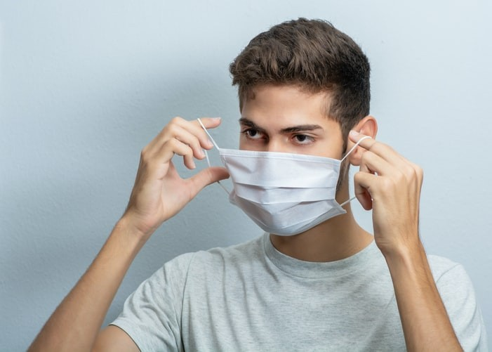 man places disposable mask on face.