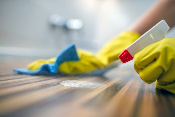 A person spraying disinfectant onto a wooden counter