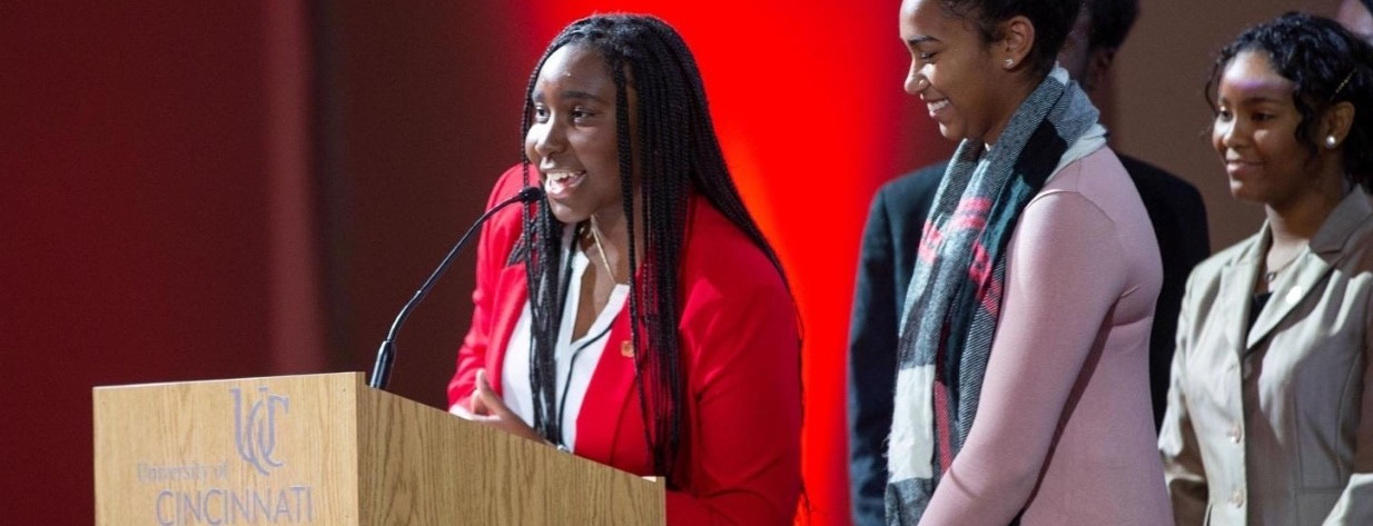 Janice Rotich delivers a speech onstage at a Darwin T. Turner scholar ceremony..
