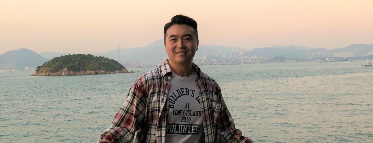 Mark Woo smiles for a photo in Hong Kong in front of a scenic ocean view.