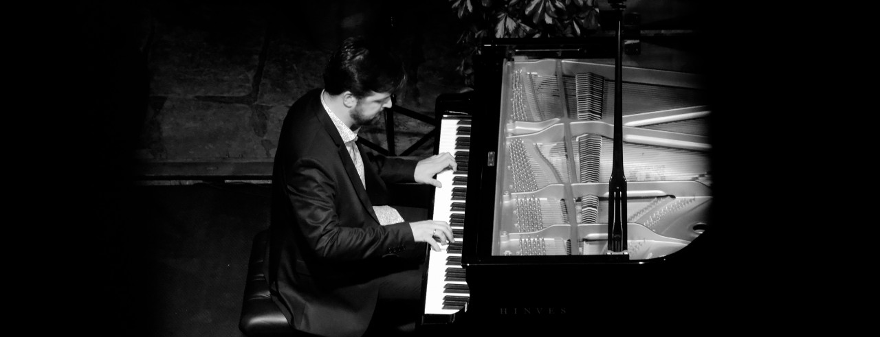 A black and white photo of CCM Assistant Professor of Jazz Piano Sergio Pamies playing piano.
