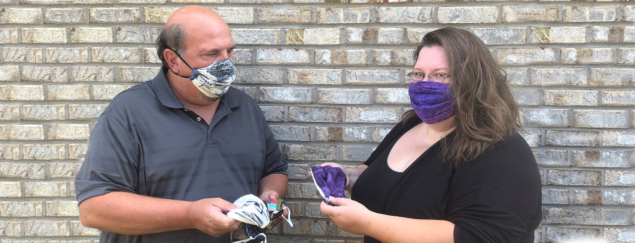 UC student Tabetha Cloke and faculty member Thomas Mobley wearing masks and showing each other more masks