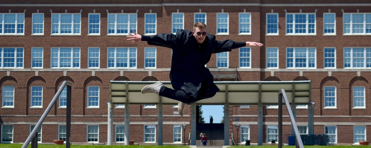 UC grad Ben Paulus jumps in the air wearing his graduation gown in front of McMicken Hall.