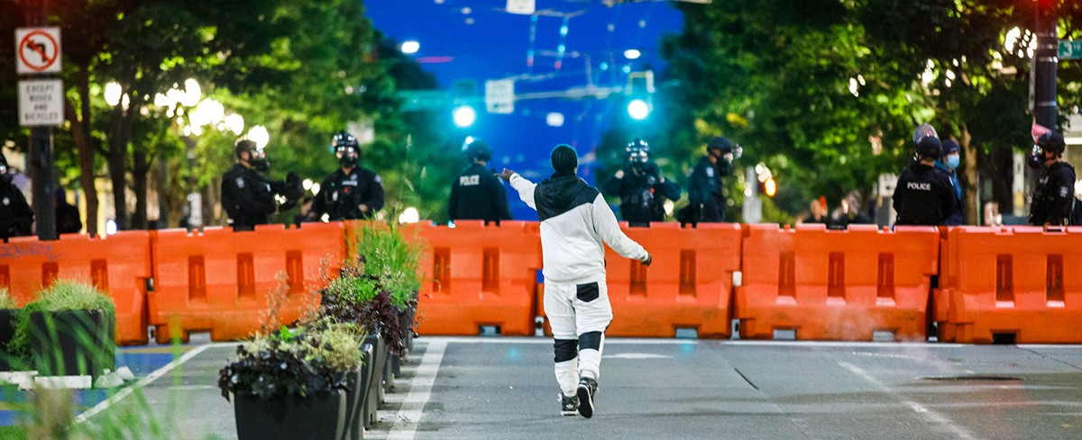 a protester stands in front of a line of police standing behind orange barricades