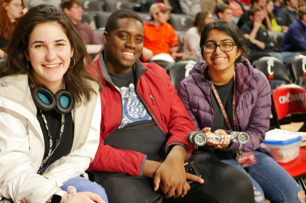 Three students at Fifth Third Arena, one student holding a robot