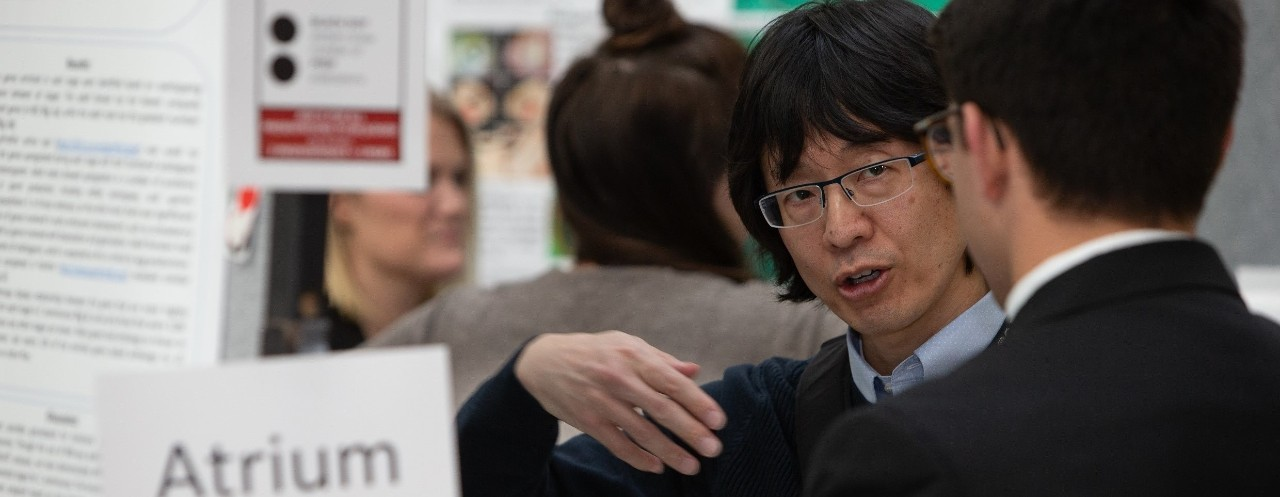 Man with glasses looks inquiringly at a younger man at a research poster showcase