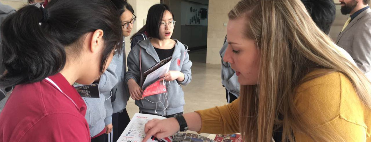 Sarah Shepherd shows a Chinese student a University of Cincinnati brochure