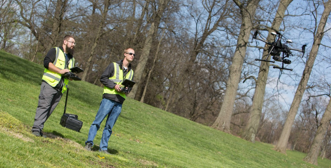Two people wearing safety vests fly a drone.