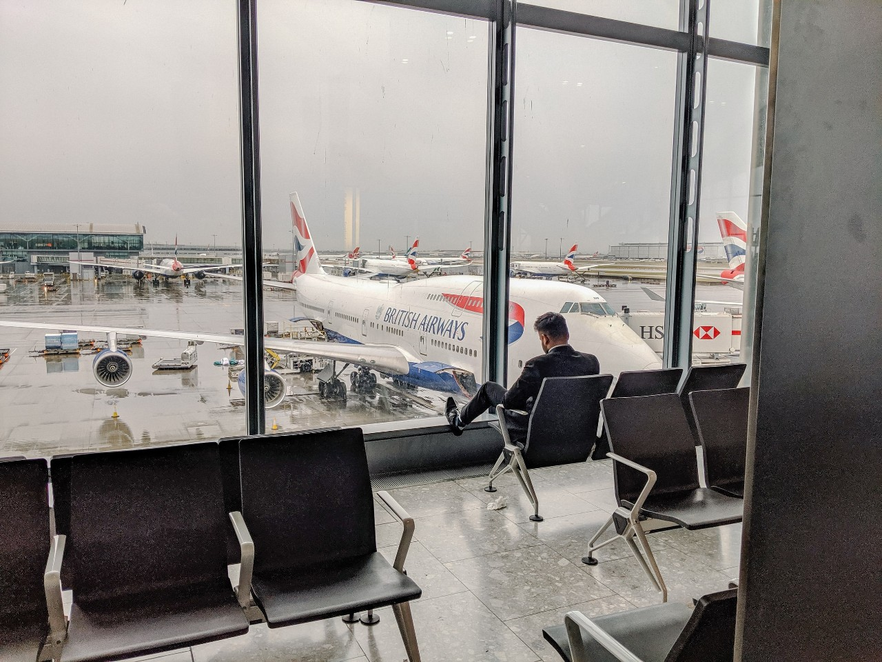 A man waits at an airport terminal overlooking an airliner.
