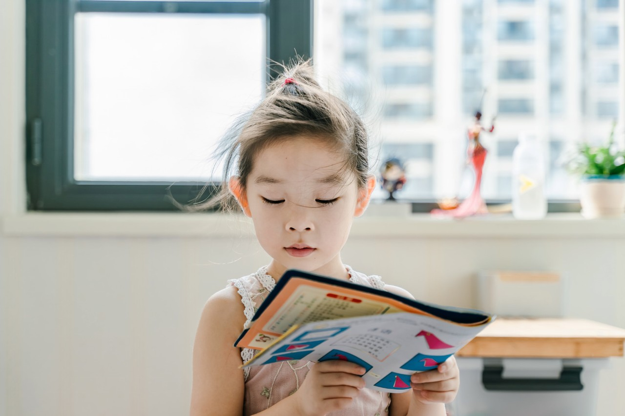 A young girl reading a magazine