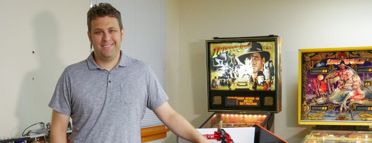 Zach Fuchs poses in his lab near pinball machines