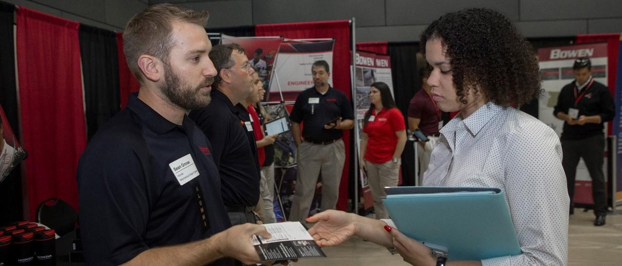 A recruiter hands a card to a job seeker at a UC career fair