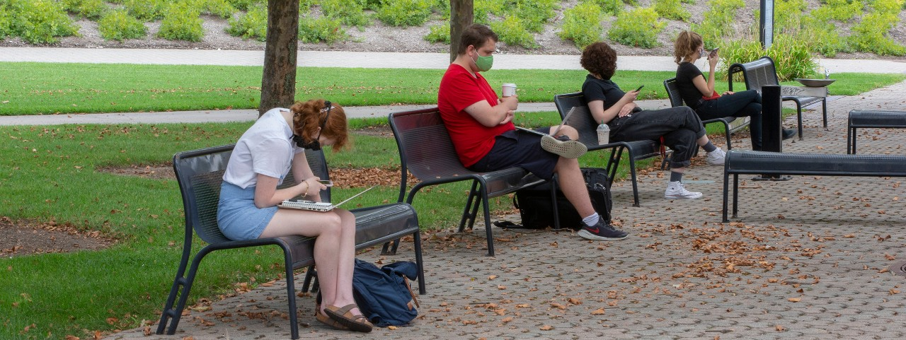 Students social distance by sitting singly on benches