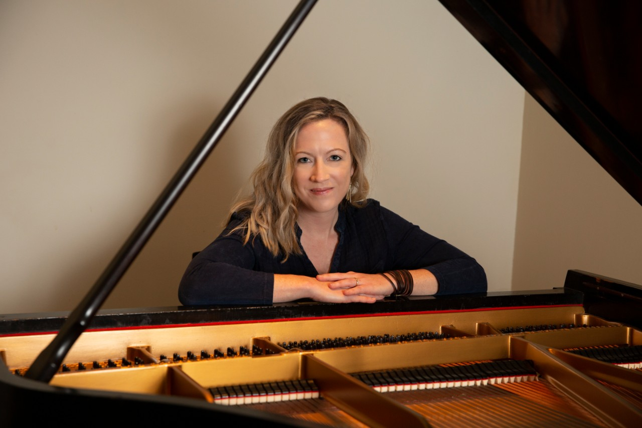 Sarah Hutchings sits at a piano and smiles
