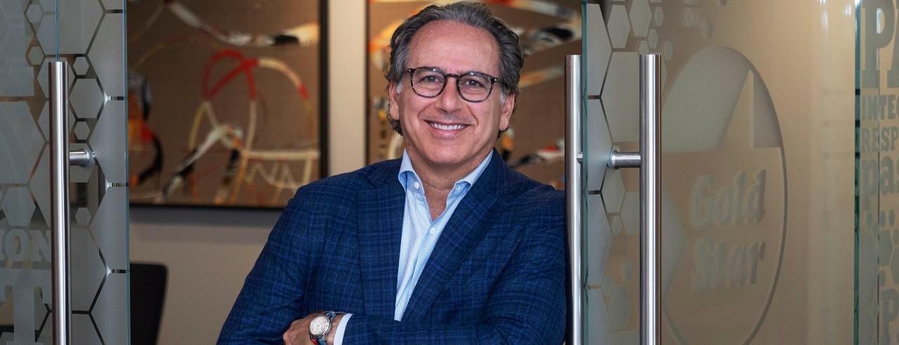 Roger David, CEO of GSR Brands, posing at glass door entrance of business.
