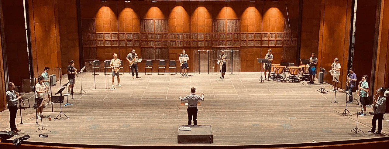 A saxophone ensemble rehearses on stage.