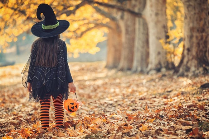 a photo of a child in a halloween costume by some trees with autumn leaves on the ground