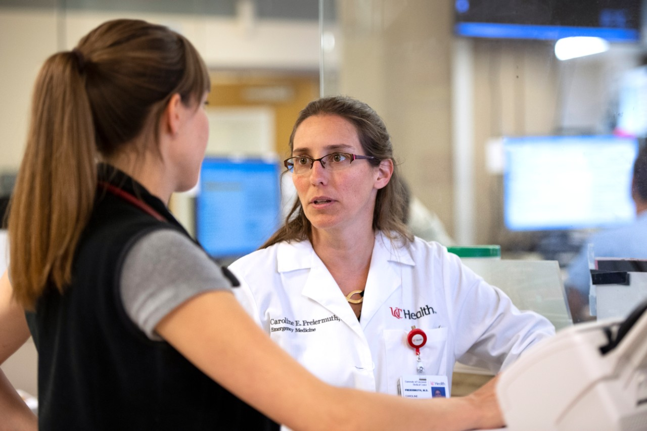 a woman doctor in a white lab coat talks to a colleague in a hospital emergency room