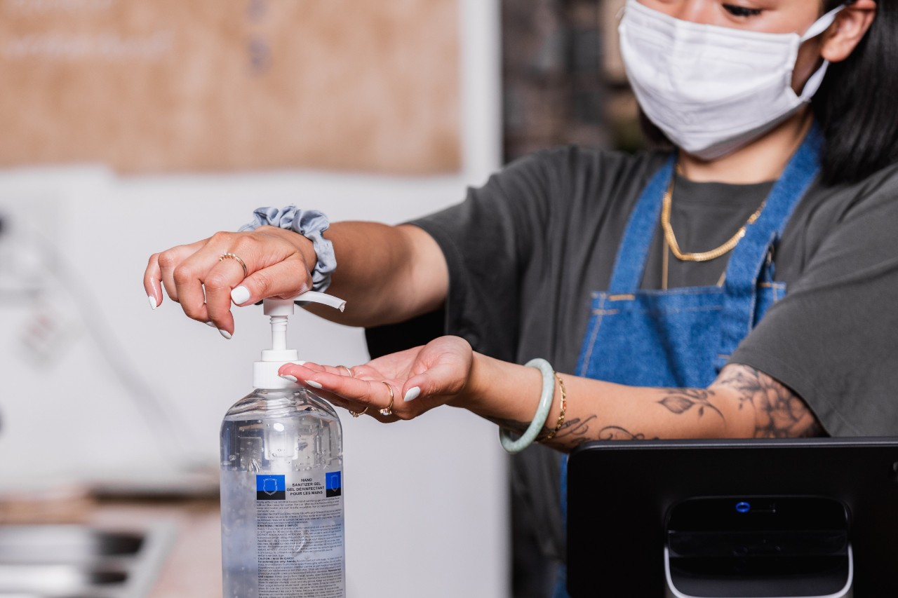 a woman wearing a mask uses hand sanitizer