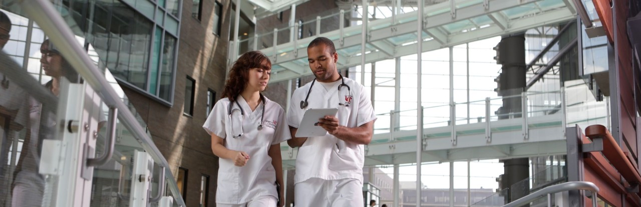 a young white woman and young black man in scrubs walk and talk in a glass-filled atrium
