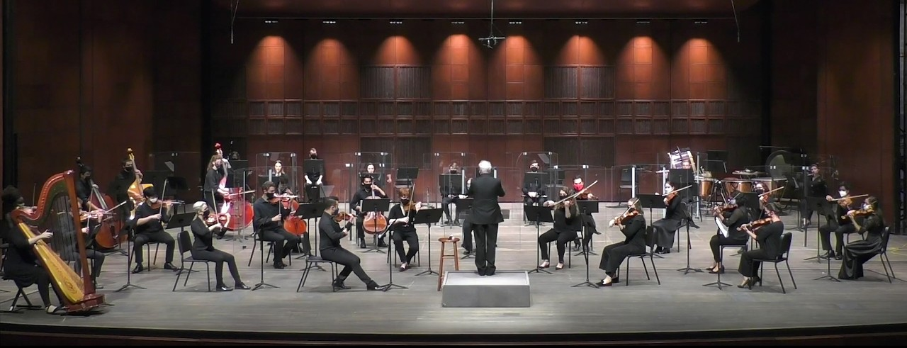 A photograph of the CCM Philharmonia performing on the stage of Corbett Auditorium.
