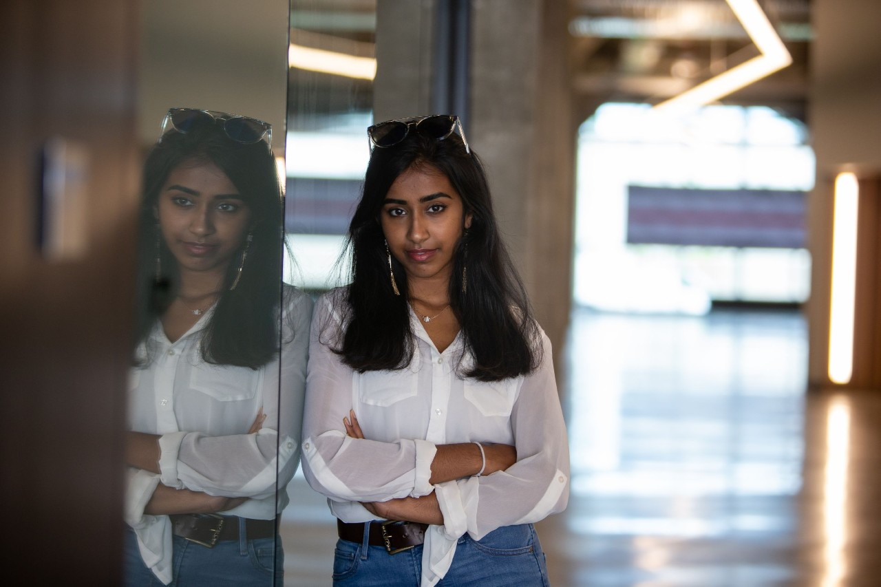 UC student stands in hallway