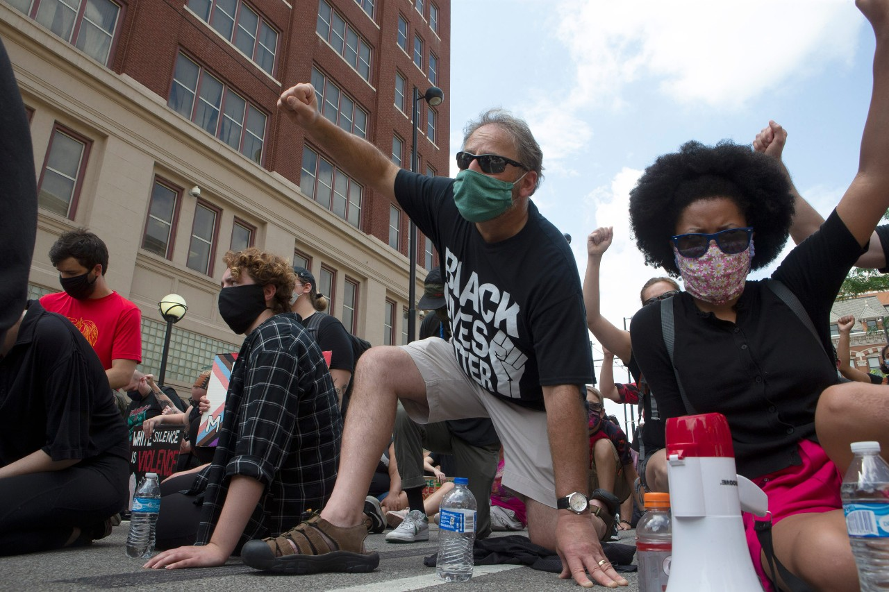 people kneeling on a Cincinnati street with their fists in the air during a protest march