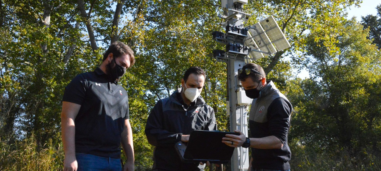 Three people wearing face masks study a laptop in front of a steel pylon mounted with electronic equipment surrounded by trees.
