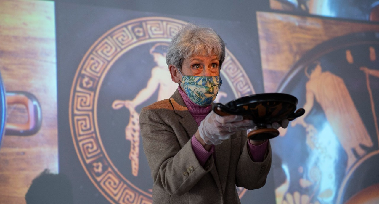 UC professor Barbara Burrell wearing a face mask holds up an ancient Greek cup in her latex-gloved hands.
