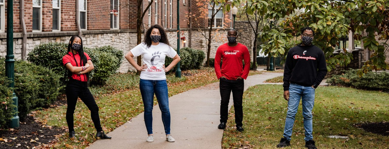 4 students in UC gear pose outside on campus