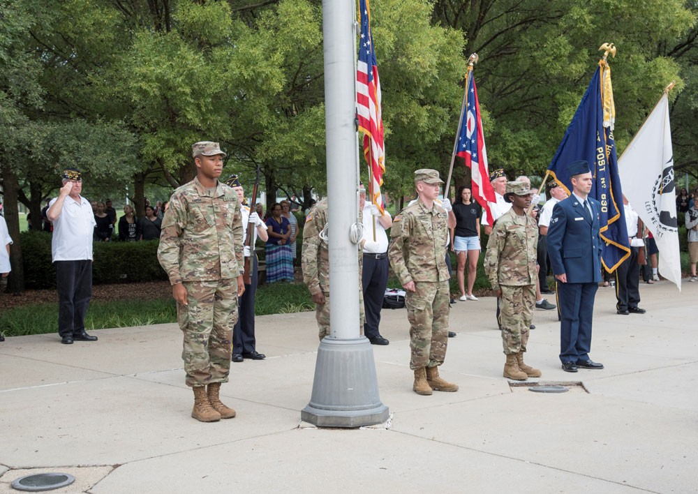 Students and members of military standing at attention during an outdoor flag ceremony