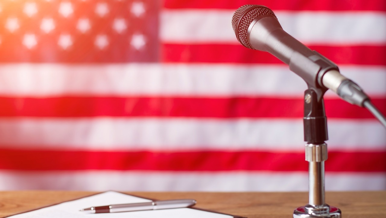 A microphone and podium in the foreground, with an American flag in the background.