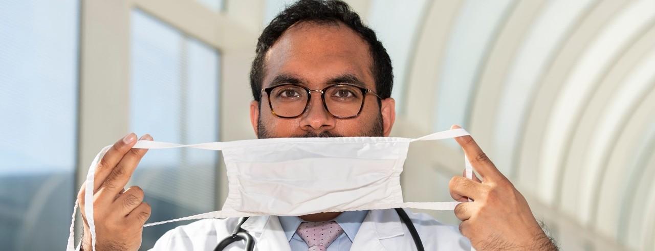 Yashu Dhamija, MD, hold a face mask