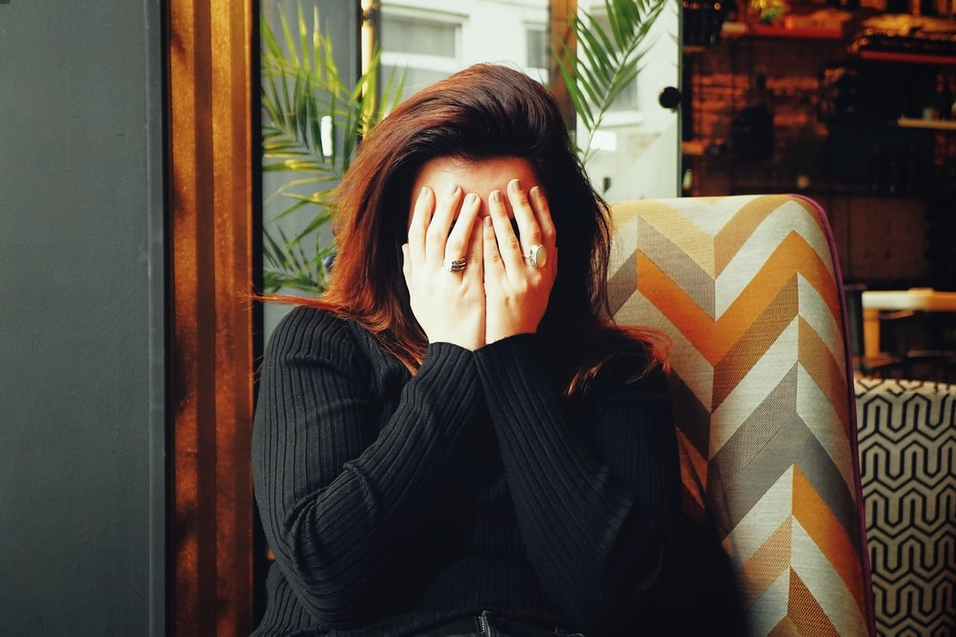 women with hands covering her face