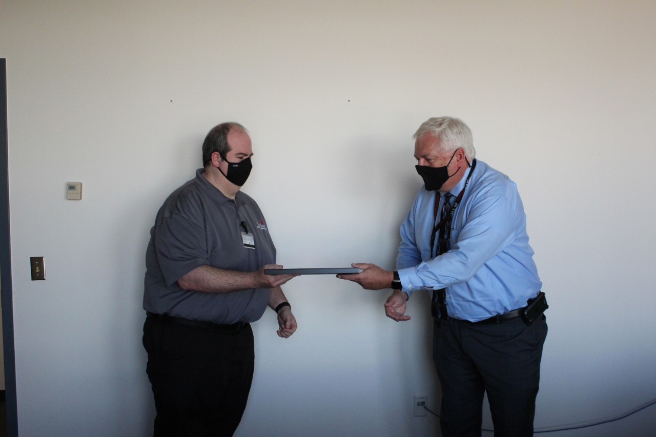 UC Public Safety Director James Whalen presents the Rave Mobile Safety SmartSave Award to Emergency Communications Dispatcher Ted Langdon.