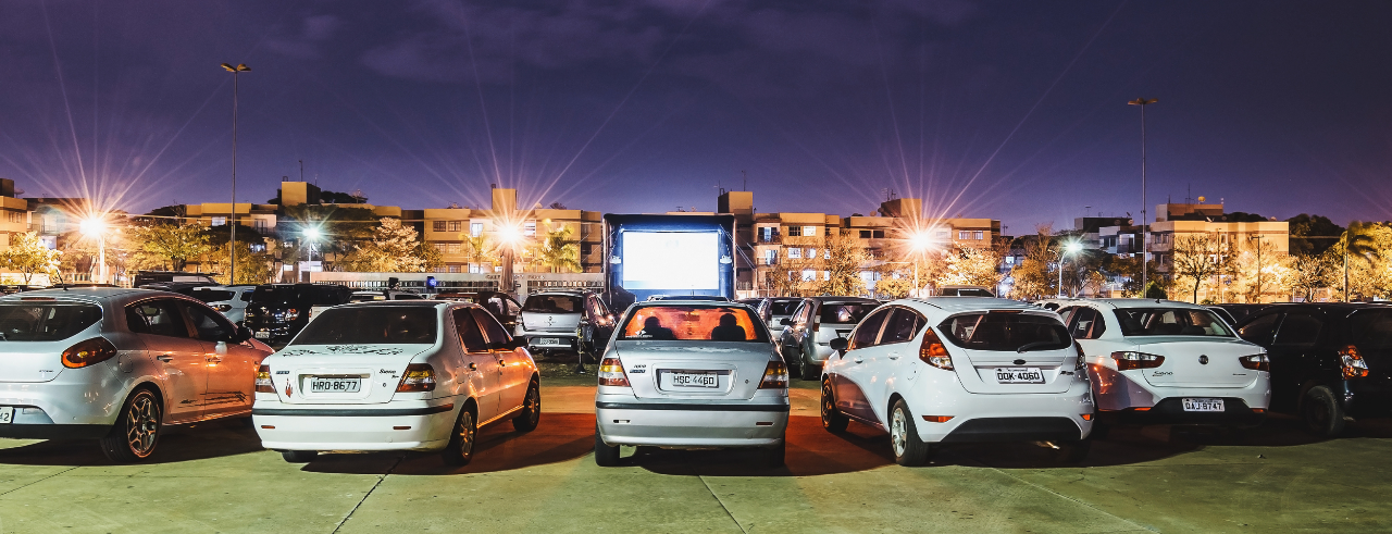 rows of cars in a parking lot, facing a large lit movie screen