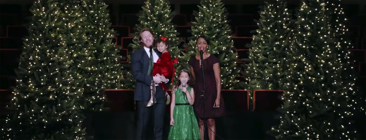 A family performs on stage during a holiday concert