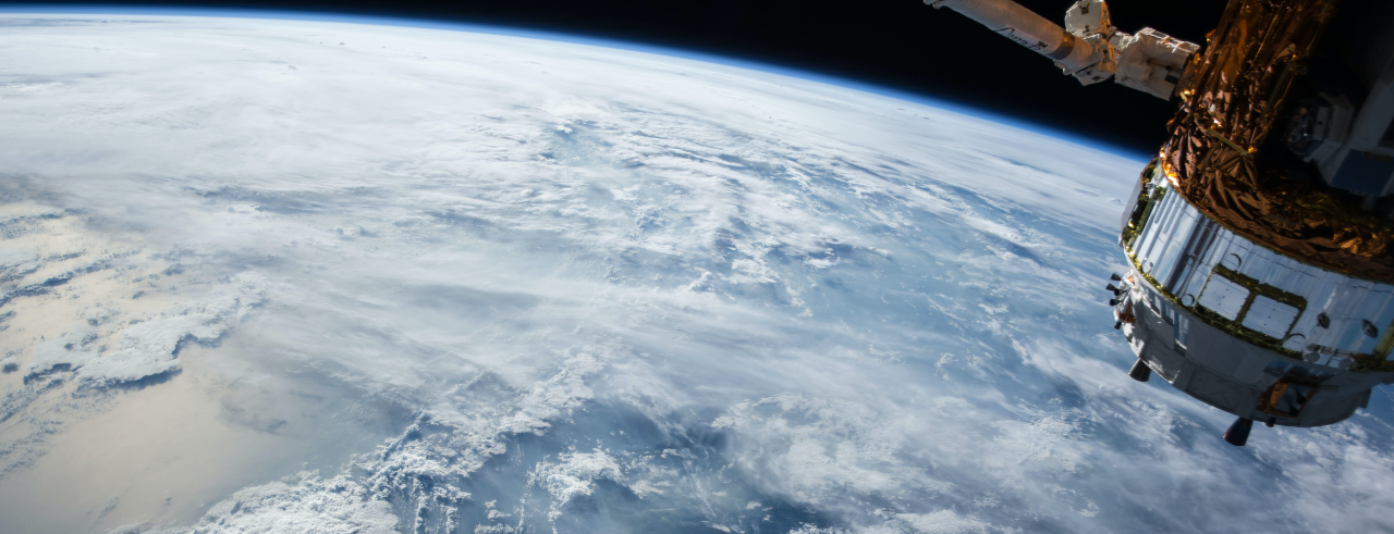 A view of Earth from space, with a satellite in the top right corner