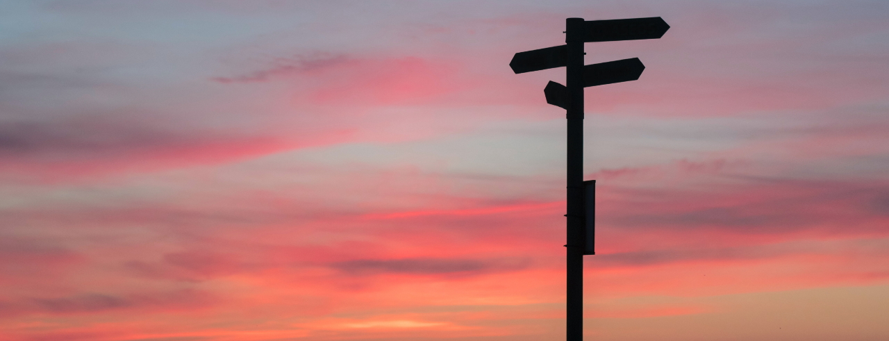 silhouette of a sign post with arrows pointing in multiple directions, with a sunset in the background