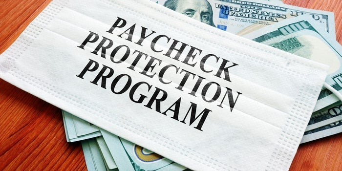 "Picture of a face mask with the words ""Payroll Protection Program"" written across the front. The mask is sitting atop a pile of $100 bills."