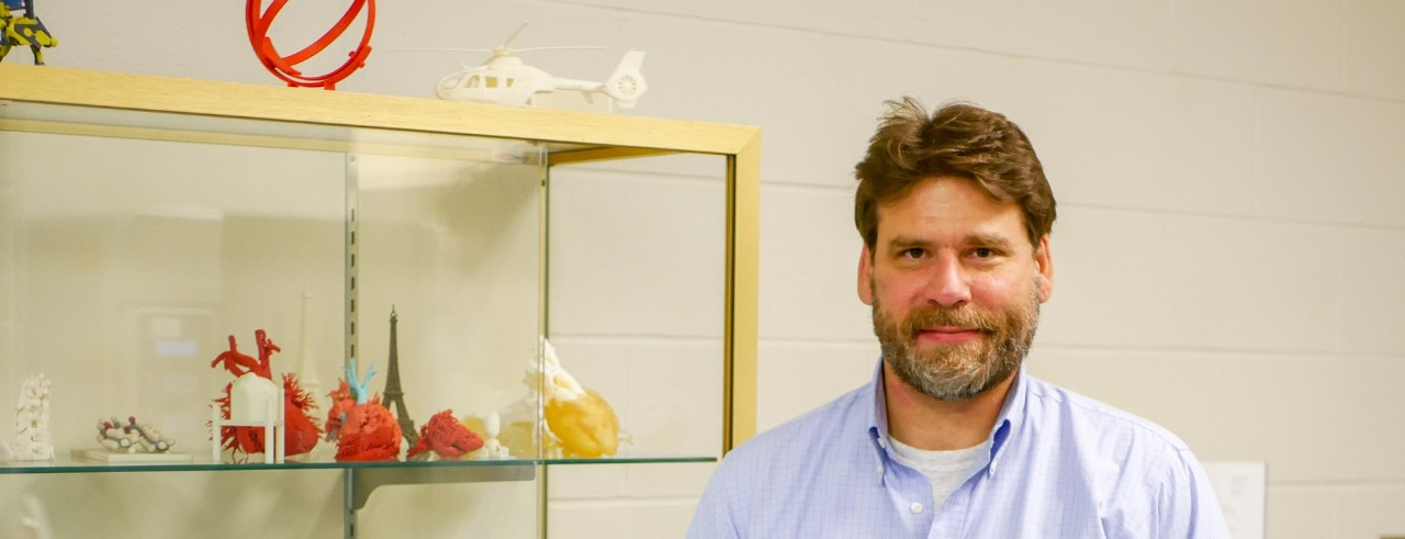 Sam Antoline with 3D-printed items from his lab