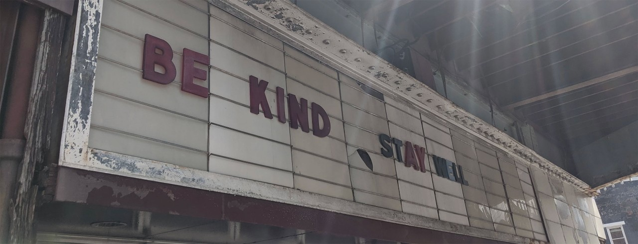 """The marquee of a theater reads """"Be kind, Stay well."""""""