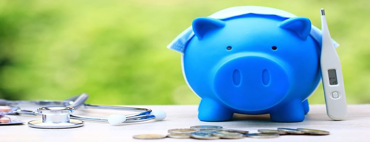 blue piggy bank with some coins and a stethoscope and thermometer