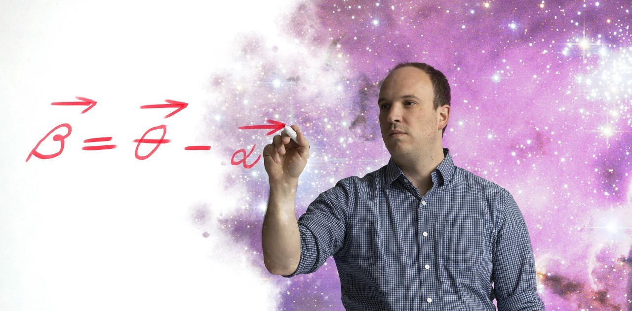 A photo illustration of Matthew Bayliss writing an equation with a starscape behind him.